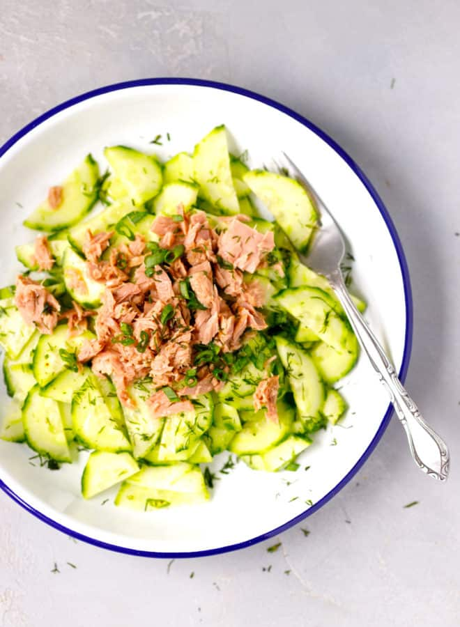 A bowl with tuna cucumber dill salad and fork inside.