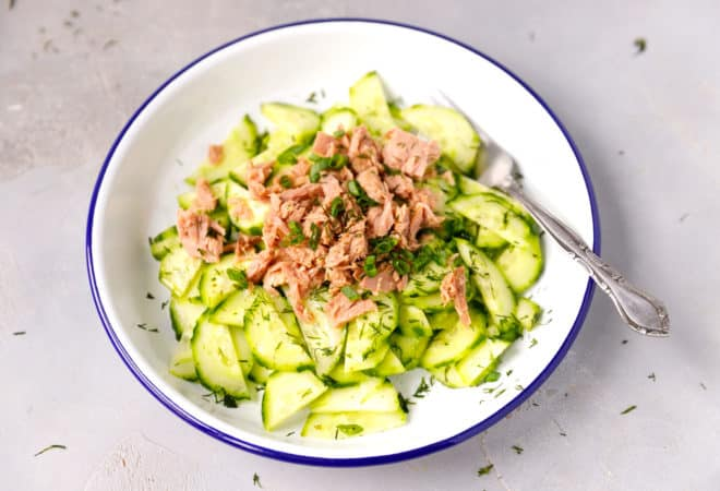 A white bowl with cucumber tuna salad inside