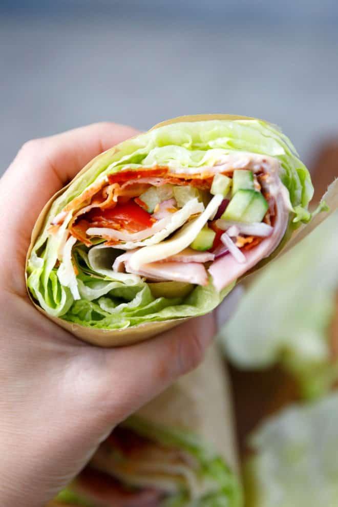 A hand holding lettuce wrap sandwich