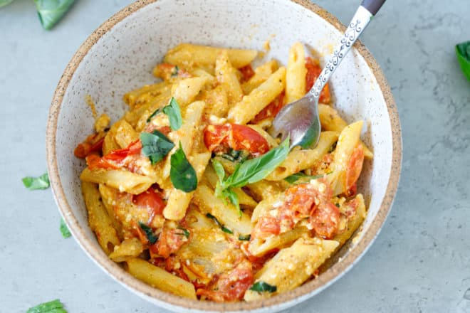 A speckled bowl of baked feta pasta with basil