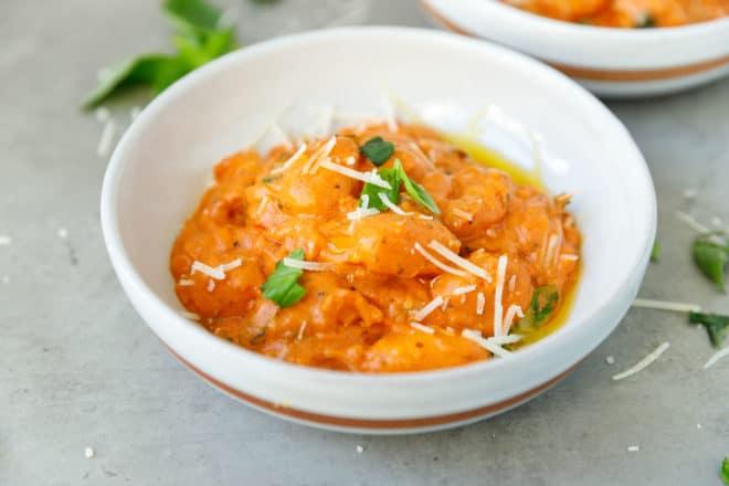 A white round bowl with creamy tomato gnocchi