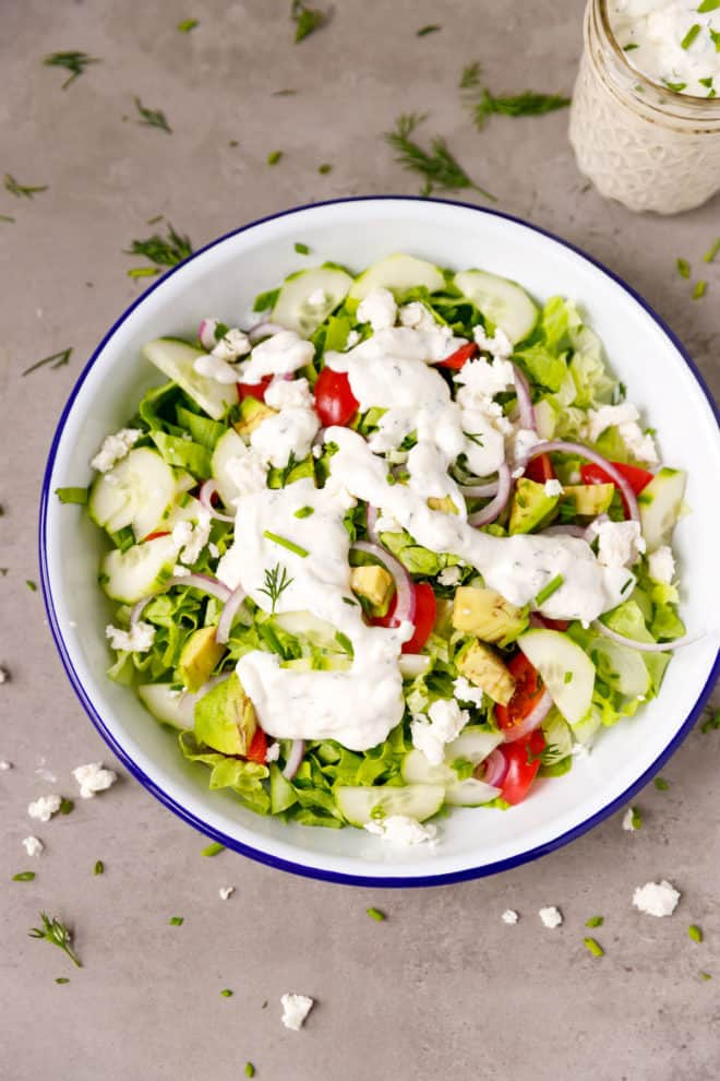 A tomato, cucumber, lettuce salad in a bowl with Feta dressing