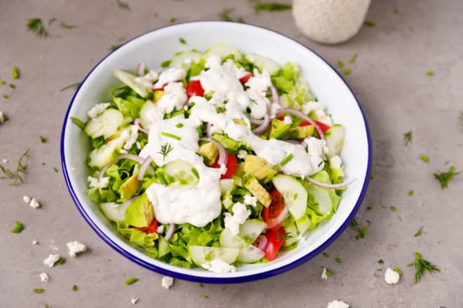 A bowl with green salad topped with Feta cheese dressing