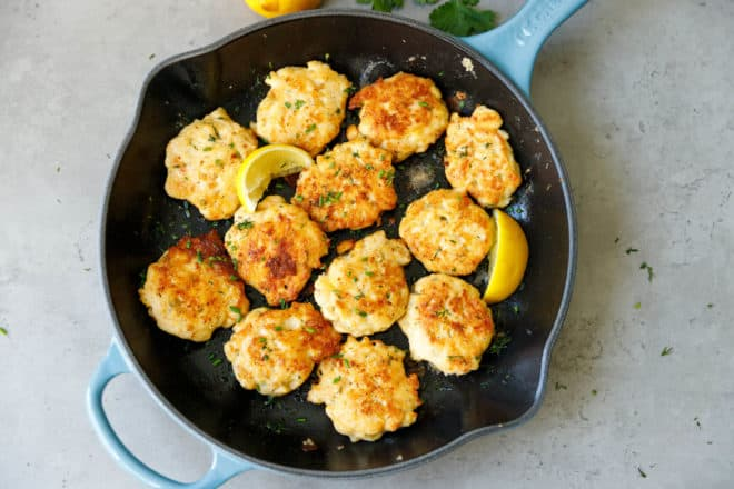 A skillet with pan fried chicken fritters