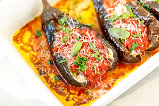 Split cut whole eggplants stuffed with tomato sauce and cheese