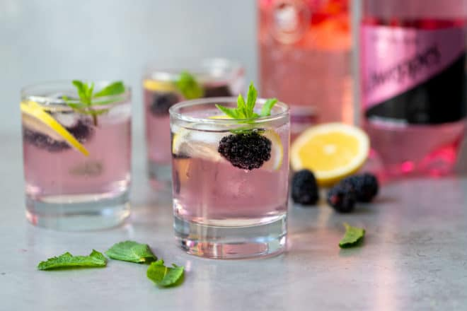 Pink gin and tonic in clear glasses topped with blackberries